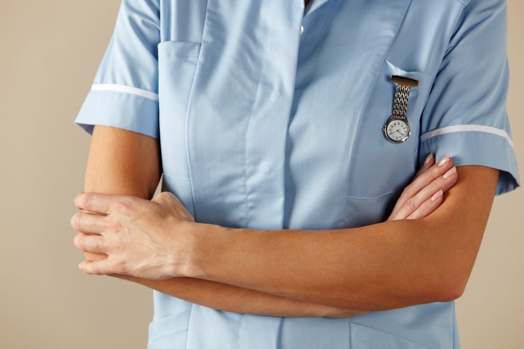 A nurse with their arms crossed.