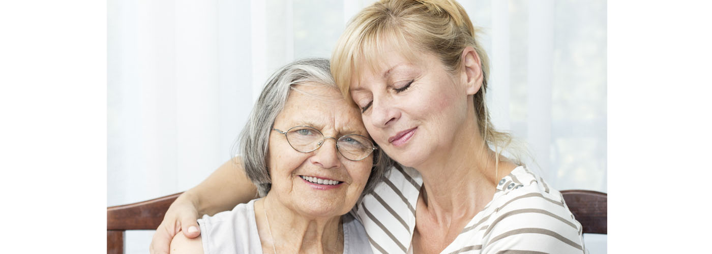 Older woman being hugged by a middle aged woman