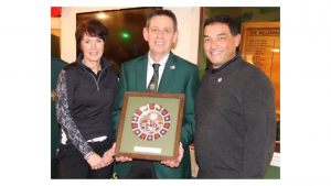 Three people stood looking at the camera. The middle person is holding a golfing plaque.