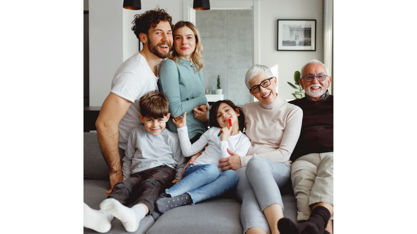 A young family with grandparents sat on a sofa.