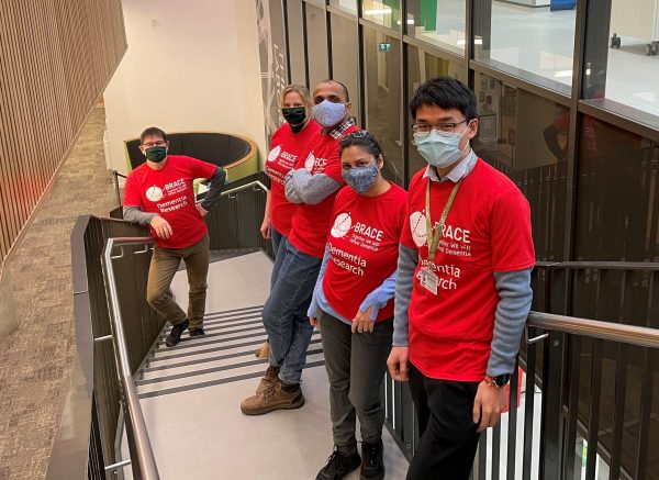 Exeter University team of 4 people standing on stairs in red BRACE t-shirts and wearing face masks