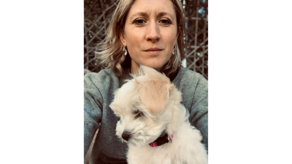 Emma Gray is looking at the camera with a small white dog.