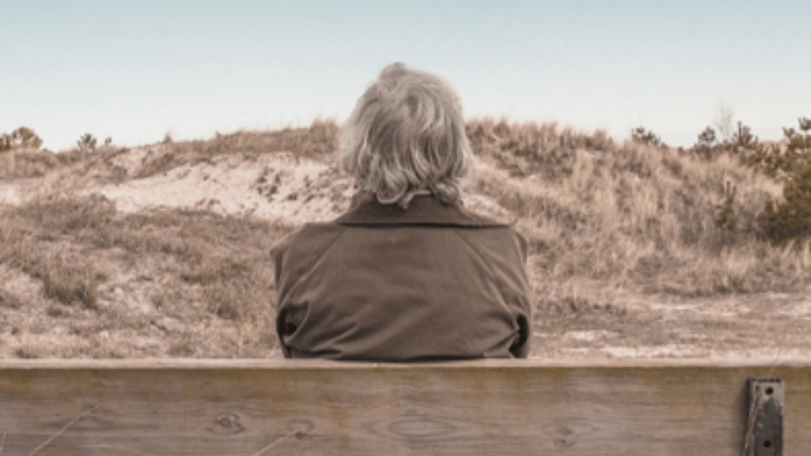 Woman sat on a bench looking away towards a hill.