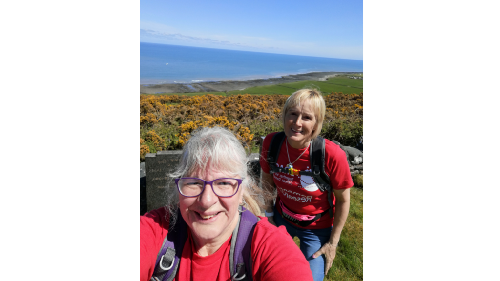 Eirlys and Linda are walking with BRACE t-shirts on, there is hills and the sea in the background