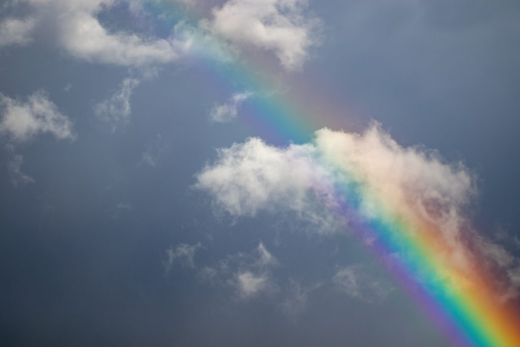 A rainbow in the sky with white clouds.