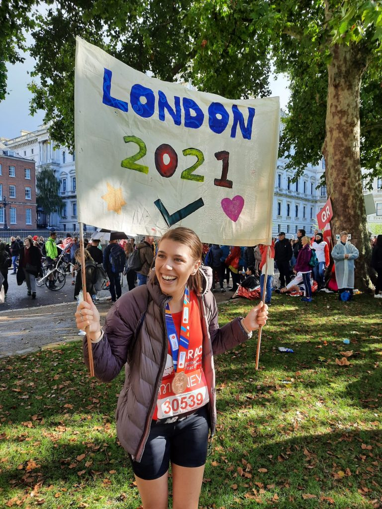 Rhiannon is stood with a banner saying London 2021