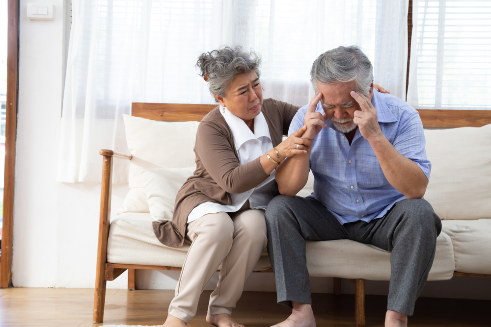 Asian senior retired couple holding hands and taking care together at home.