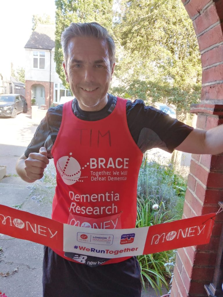 Tim is stood in his BRACE top pretending to finish the marathon at his home.