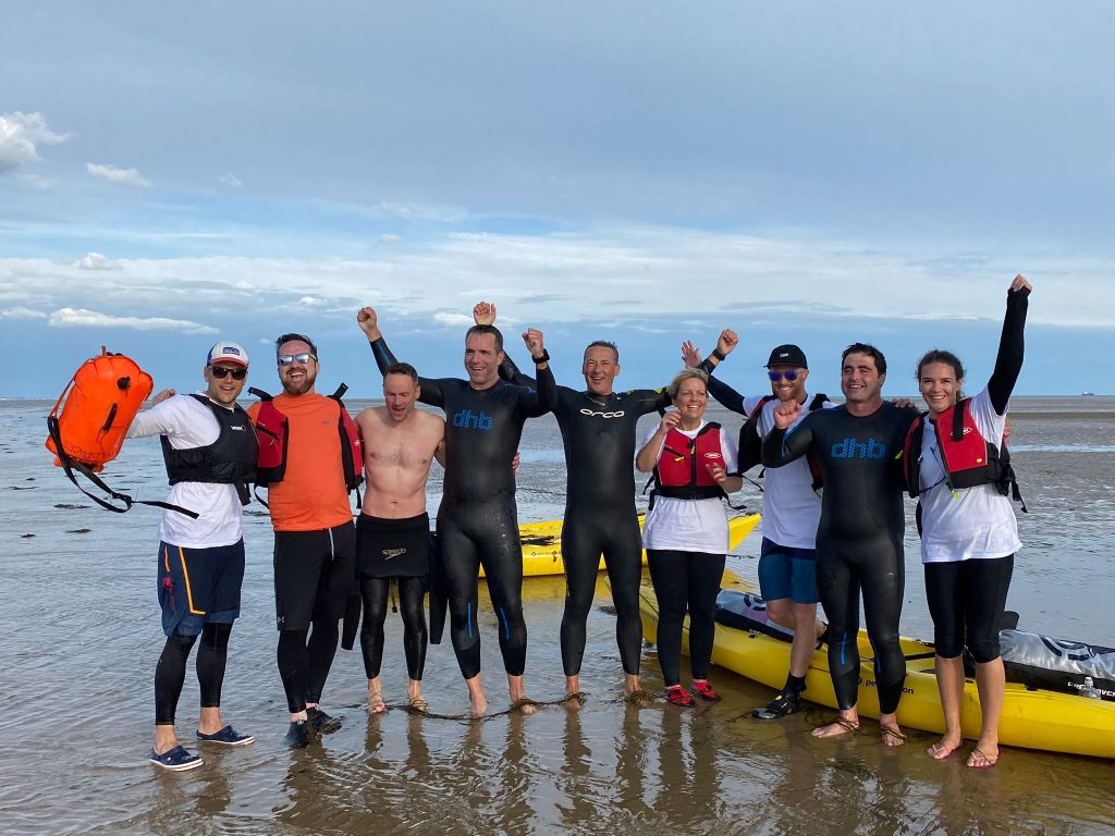 10 swimmers stood on the beach in wetsuits by the sea