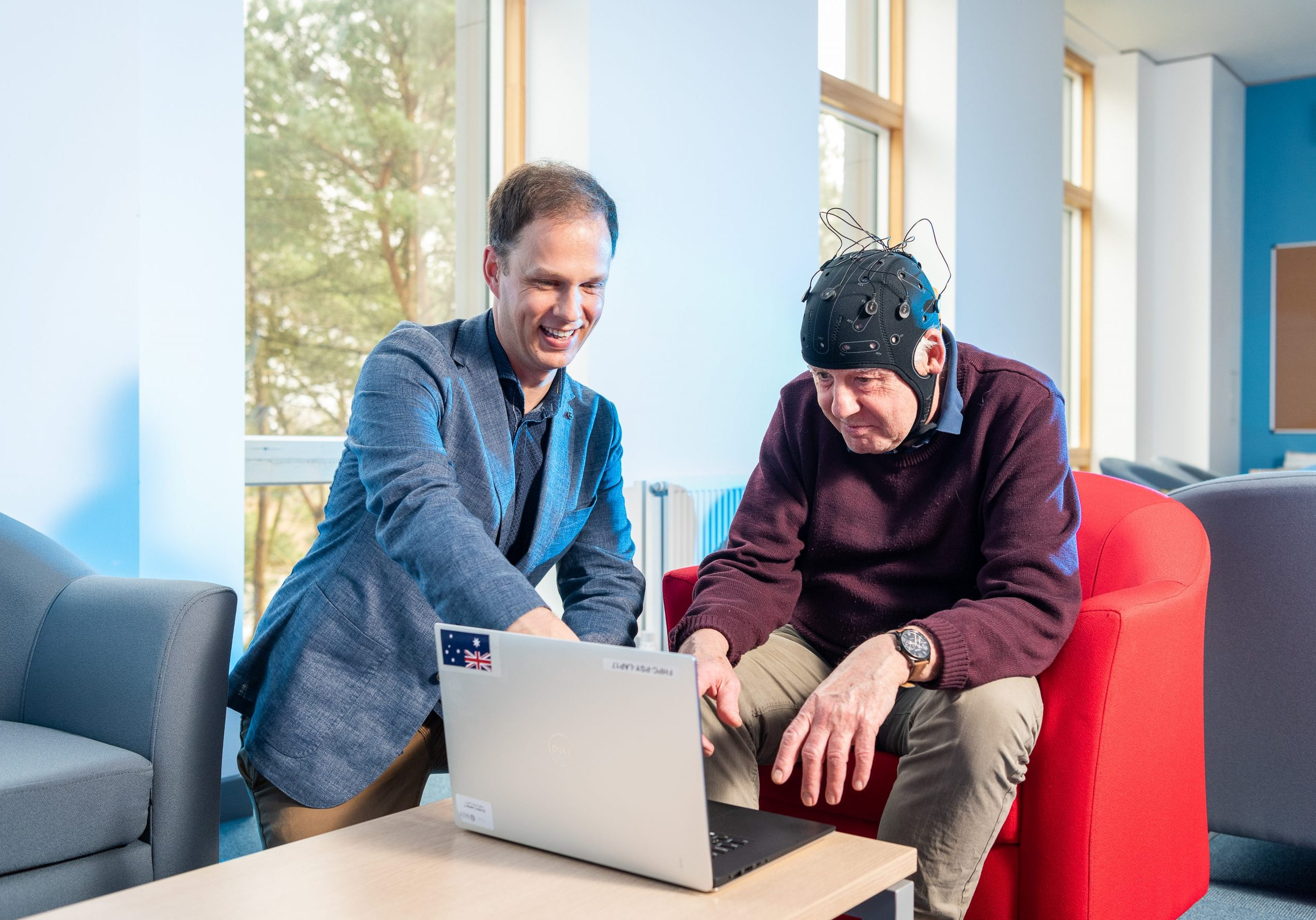 Dr George Stothart is sad next to an older man wearing the EEG headset and both are looking at a laptop on a small table.