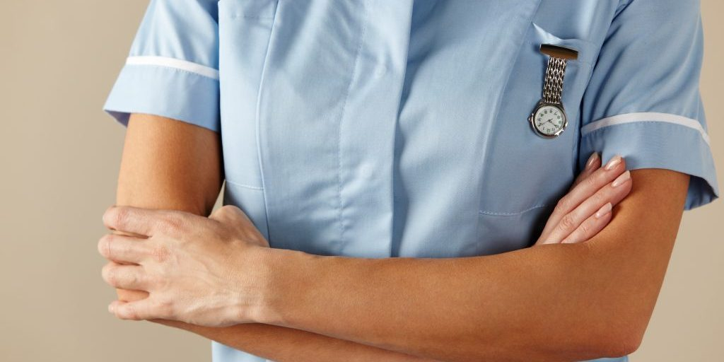 Torso of a nurse with her arms crossed.