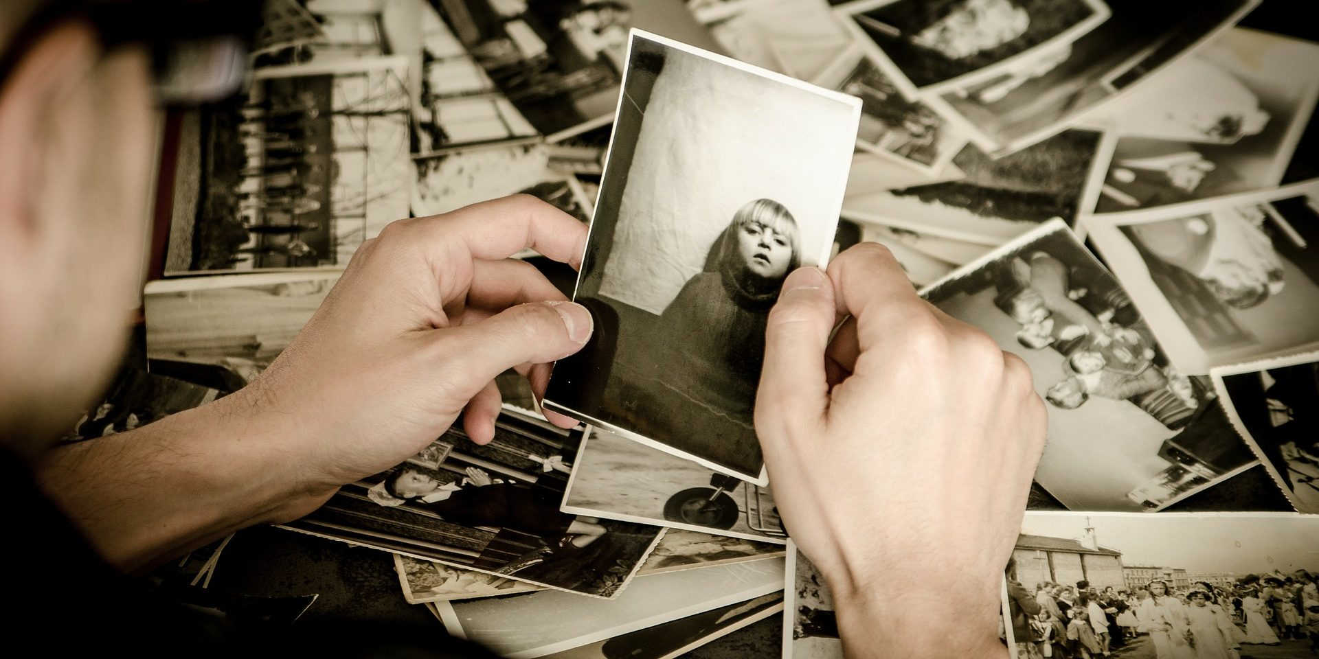 Black and white photos laid on table. The back of a person's head, with their hands holding a photo.