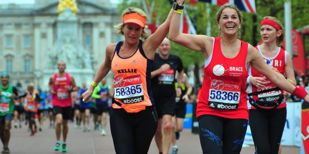 Two women holding hands and running towards the end of the London Marathon